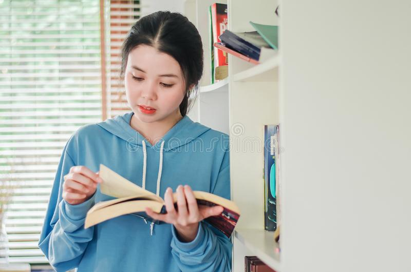 Beautiful young girl standing in the library at home with books, Woman reading a book stock photo