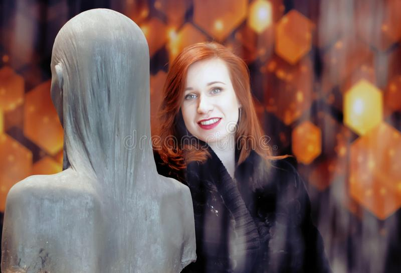 Beautiful, young girl with beautiful, natural make-up and red lipstick, red hair and black clothes stands behind the fountain royalty free stock photos
