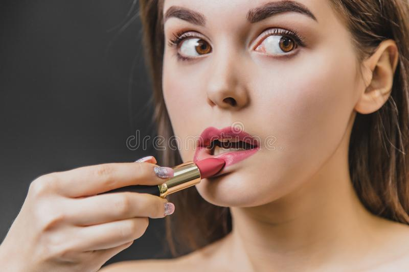 Beautiful young girl stands on a black background. During this, the lipstick is painted lipstick close-up. stock photos