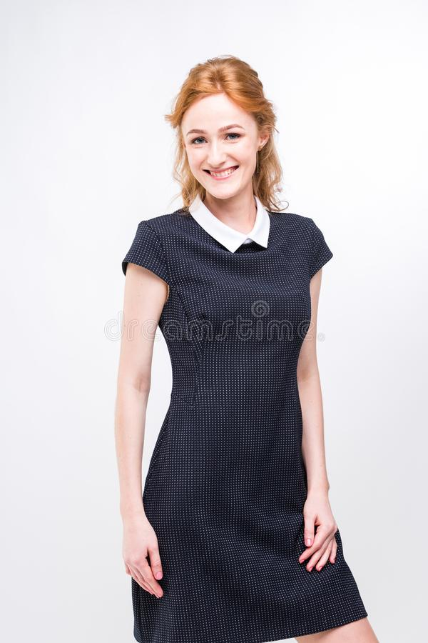 Beautiful young girl student, secretary or business lady with charming smile and red curly hair in black dress in white royalty free stock photography