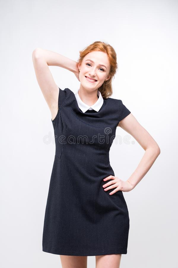 Beautiful young girl student, secretary or business lady with charming smile and red curly hair in black dress in white stock photo