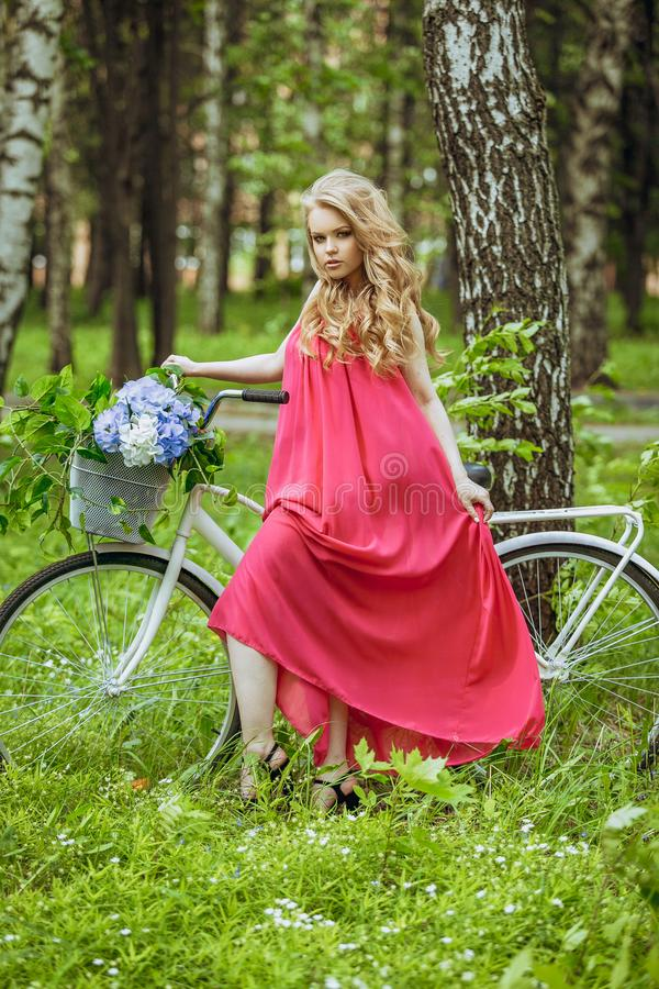 Beautiful young girl in a summer dress at sunset. Fashion photo in the forest. Model on a bicycle with flower bouquet, in a pink l stock photography