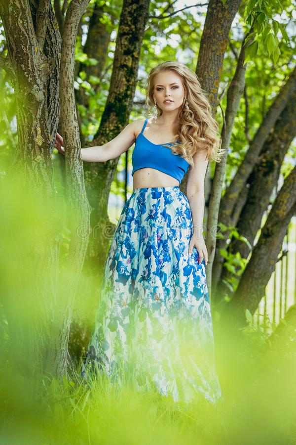 Beautiful young girl in a summer dress at sunset. Fashion photo in the forest. Model in a blue top and long skirt, with flowing cu royalty free stock photos