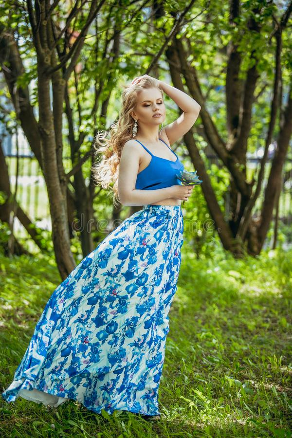 Beautiful young girl in a summer dress at sunset. Fashion photo in the forest. Model in blue top and long skirt, with flowing hair royalty free stock photography