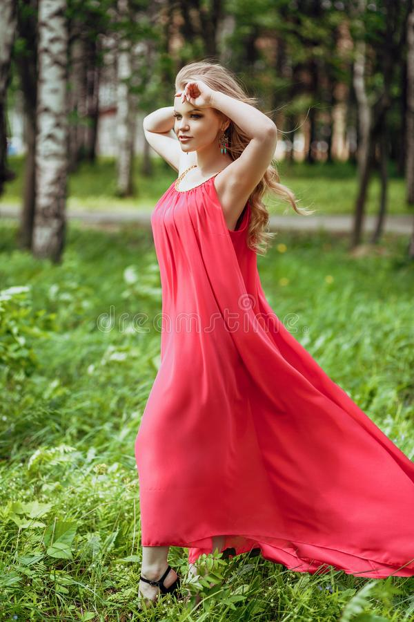 Beautiful young girl in a summer dress at sunset. Fashion photo in the forest. Model in a pink long dress, with flowing curly hair stock photos