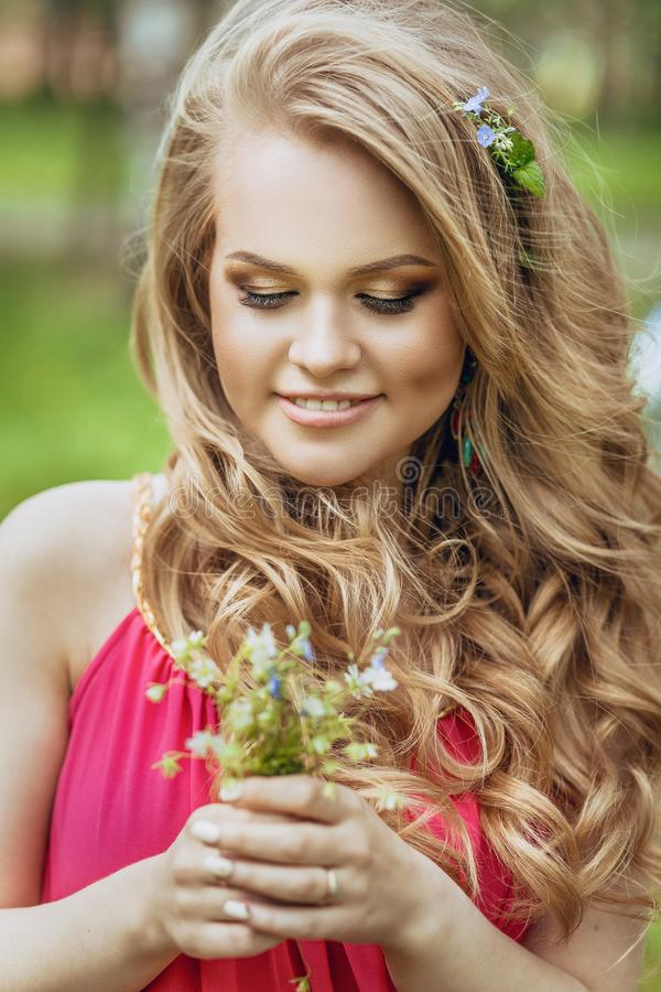 Beautiful young girl in a summer dress at sunset. Fashion photo in the forest. Model in a pink long dress, with flowing curly hair royalty free stock images