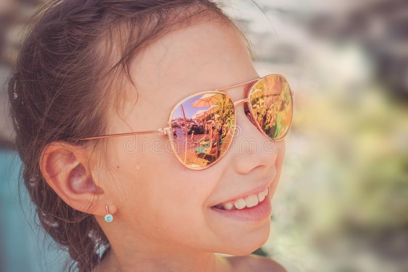 Beautiful young girl in sunglasses with beach reflection. stock photography
