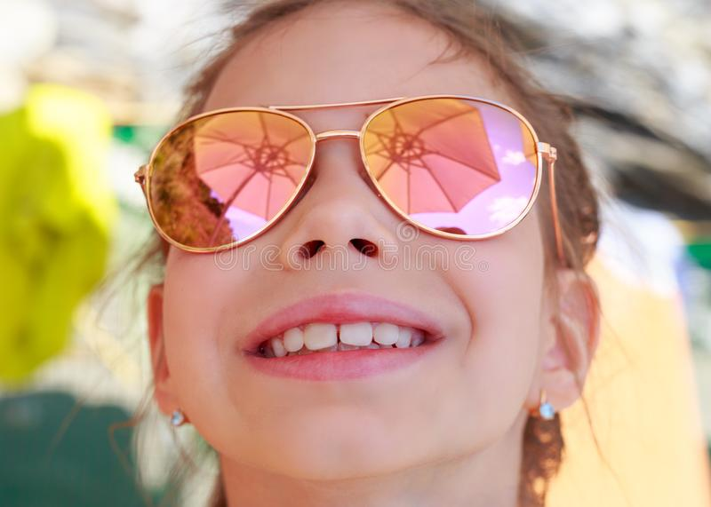 Beautiful young girl in sunglasses with beach umbrella reflection. royalty free stock photography