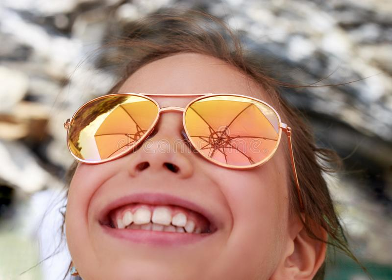 Beautiful young girl in sunglasses with beach umbrella rerlection. royalty free stock photos