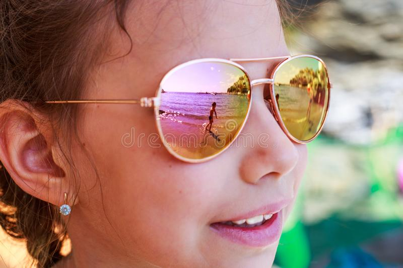 Beautiful young girl in sunglasses with sea reflection. royalty free stock images