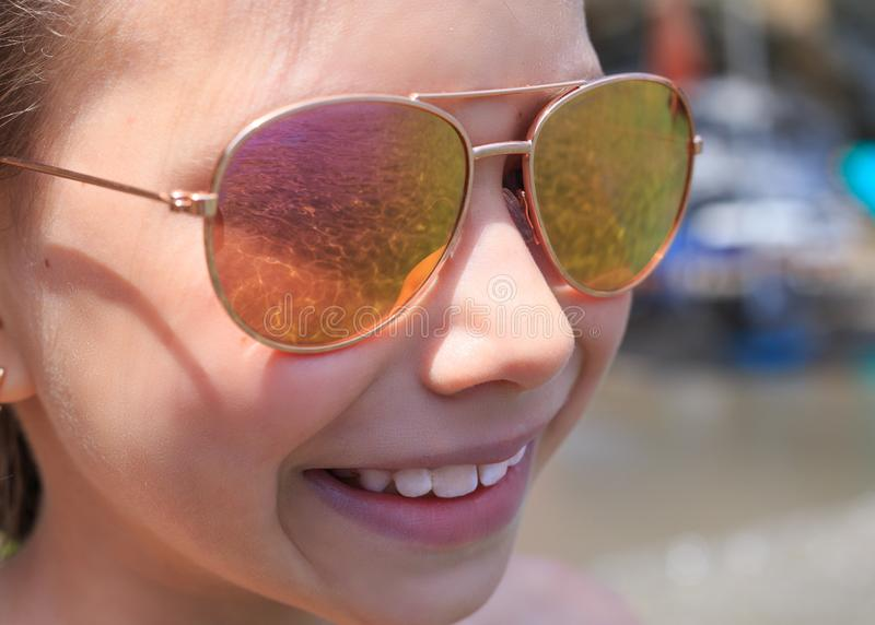 Beautiful young girl in sunglasses with sea rerlection. stock photo