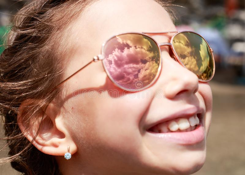 Beautiful young girl in sunglasses with sky rerlection. stock photography