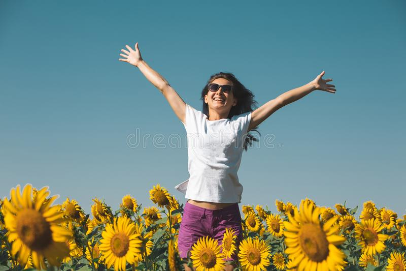 Beautiful Young Girl In Sunglasses Stands In Sunflowers With Hands Up And Smiling. Beautiful young girl with blue hair standing in a field with sunflowers with stock photo
