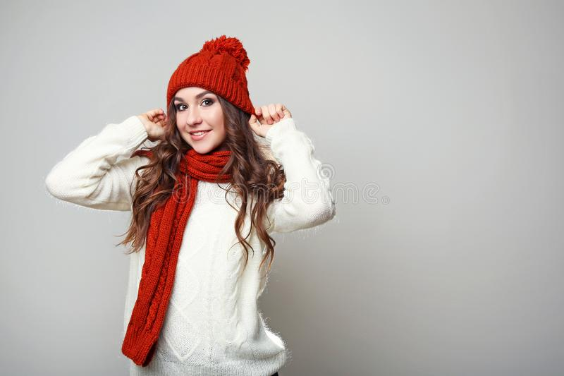Young girl in sweater, scarf and hat. Beautiful young girl in sweater, scarf and hat on grey background stock image