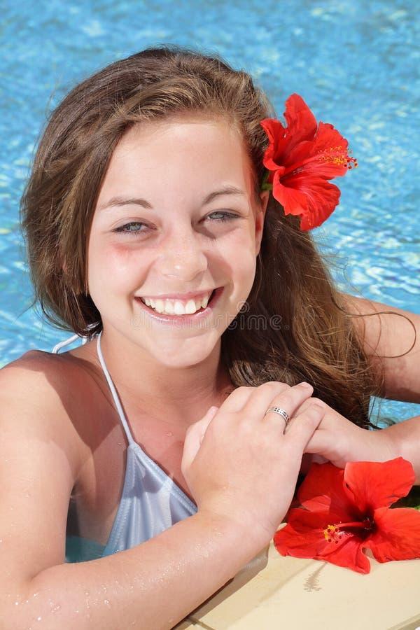 Beautiful young girl in swimming pool. Beautiful smiling young girl in a swimming pool royalty free stock image