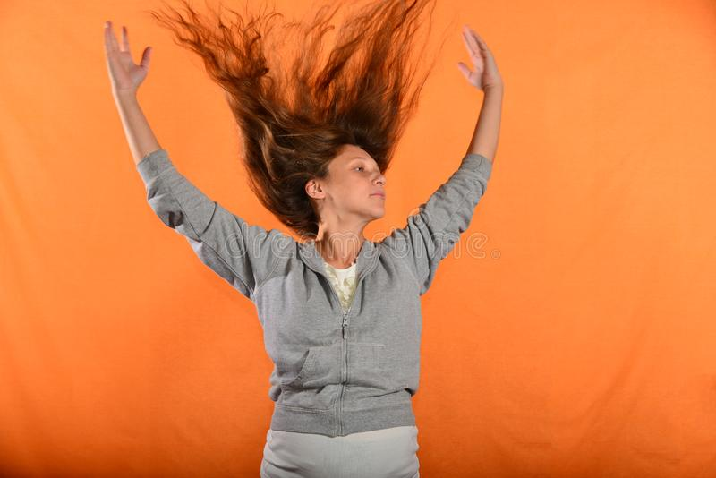 Beautiful and young girl throws up hair and holds hands in sides, concept of freedom and independence.  royalty free stock photography