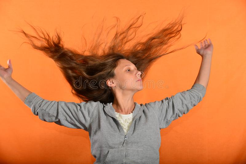 Beautiful and young girl throws up hair and holds hands in sides, concept of freedom and independence.  royalty free stock images