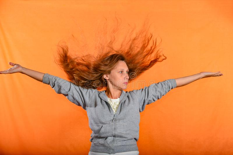 Beautiful and young girl throws up hair and holds hands in sides, concept of freedom and independence.  stock photo