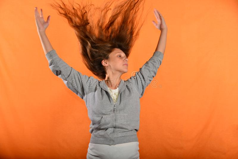 Beautiful and young girl throws up hair and holds hands in sides, concept of freedom and independence.  stock images