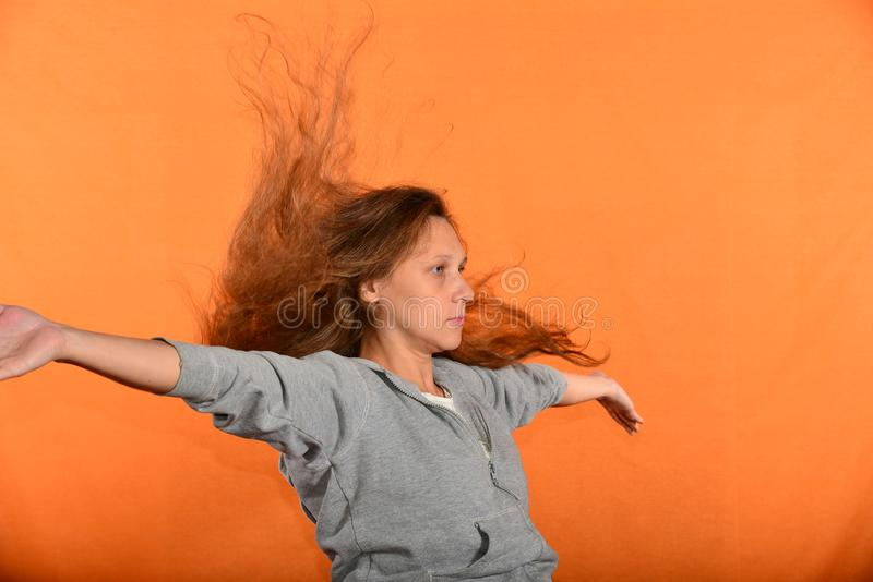 Beautiful and young girl throws up hair and holds hands in sides, concept of freedom and independence.  stock image
