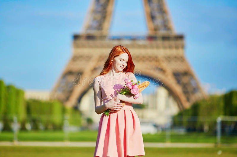 Girl with traditional French bread baguette and flowers in front of the Eiffel tower royalty free stock photography