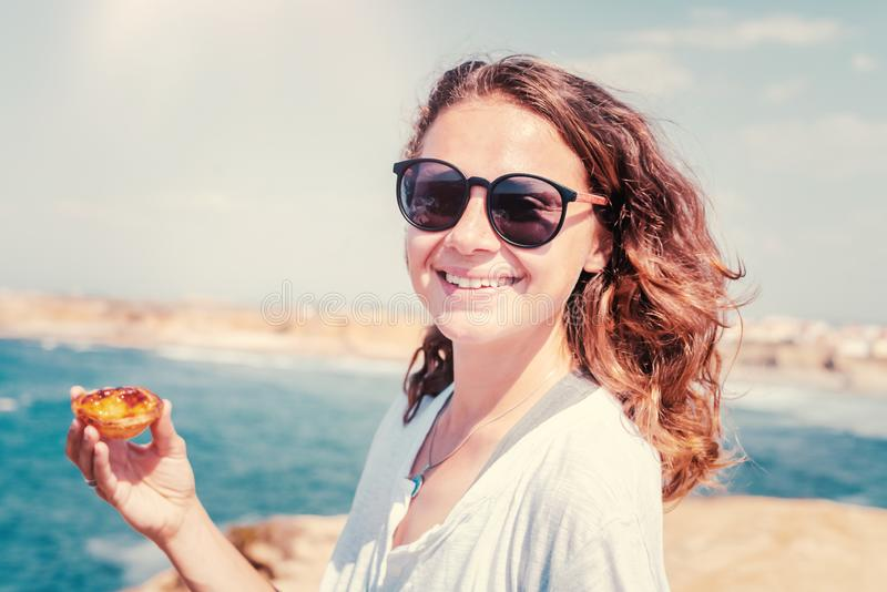 Beautiful young girl with a traditional Portuguese dessert in her hands on the background of the ocean in Portugal, travel to the stock photos