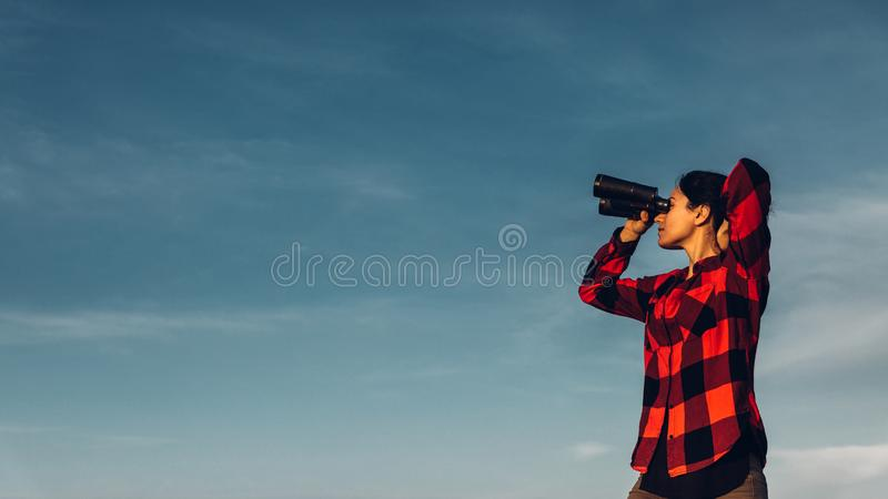 Beautiful young girl traveler looks through binoculars against a blue sky with copy space. The concept of search, motivation, royalty free stock image