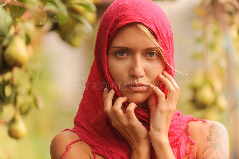 Beautiful young girl trying on a red scarf. Autumn time for harvest. Orchard. The concept of harvesting stock photography