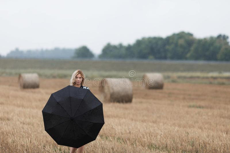 A beautiful young girl with an umbrella is standing in a field near a haystack. stock photography