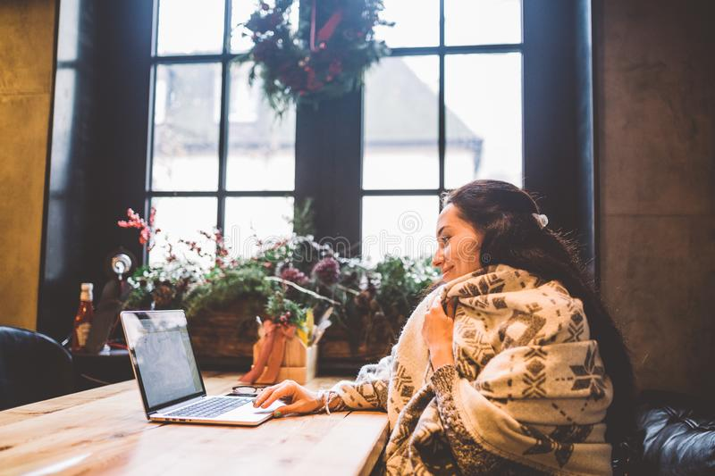 Beautiful young girl uses laptop technology, types text looking at the monitor in a cafe by the window at wooden table, in winter royalty free stock photo