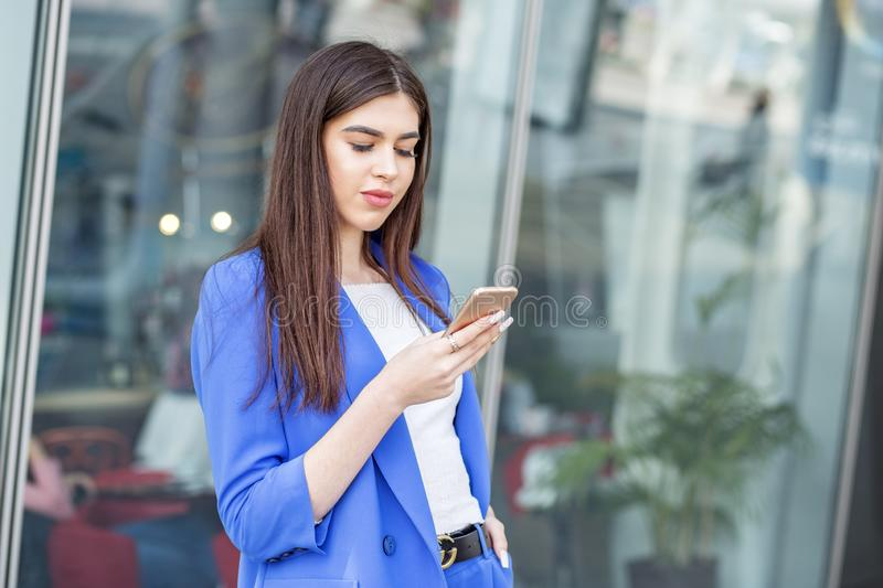 Beautiful young girl is using the internet on a smartphone. The concept of fashion, business, communication and lifestyle royalty free stock photo