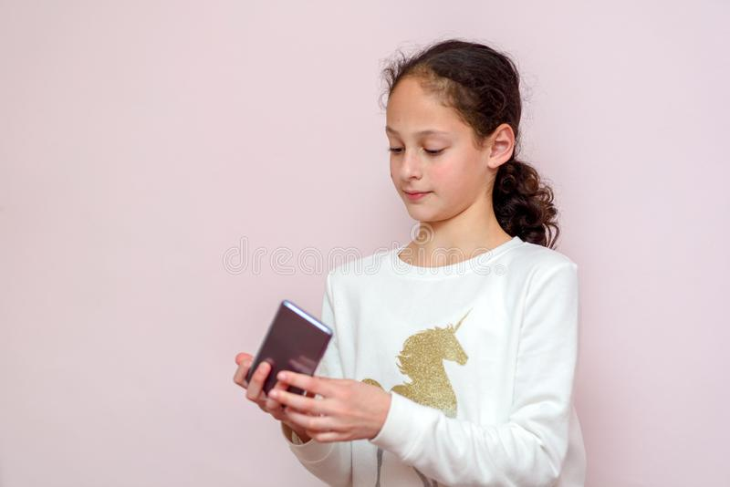 Beautiful young girl using modern smartpone, hipster child blogger typing text message on her cellphone. stock photos