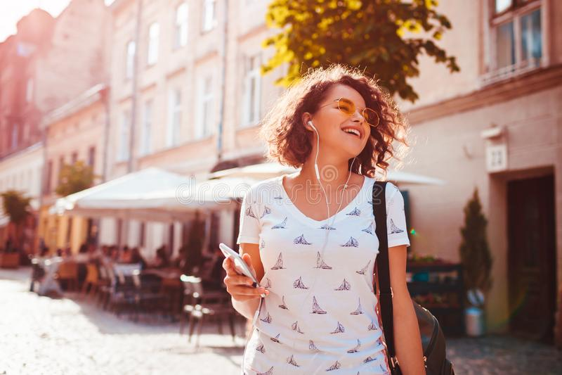 Beautiful young girl using smartphone and listening to the music walking on street. Woman dancing and singing. Beautiful young girl using smartphone and stock image