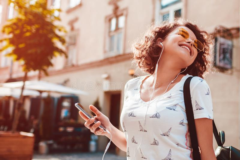 Beautiful young girl using smartphone and listening to the music walking on street. Woman dancing and singing. Beautiful young girl using smartphone and royalty free stock photo