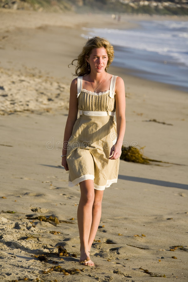 Beautiful Young Girl Walking on the Beach. At Sunset in a Dress royalty free stock images