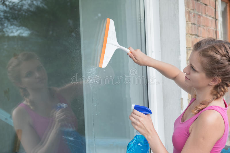 Beautiful young girl washes a window in a brick house royalty free stock images