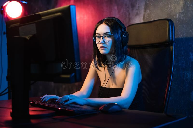Beautiful young girl wearing glasses and gaming headset plays online game on gaming PC in dark area. Streaming online. Games on internet stock photo