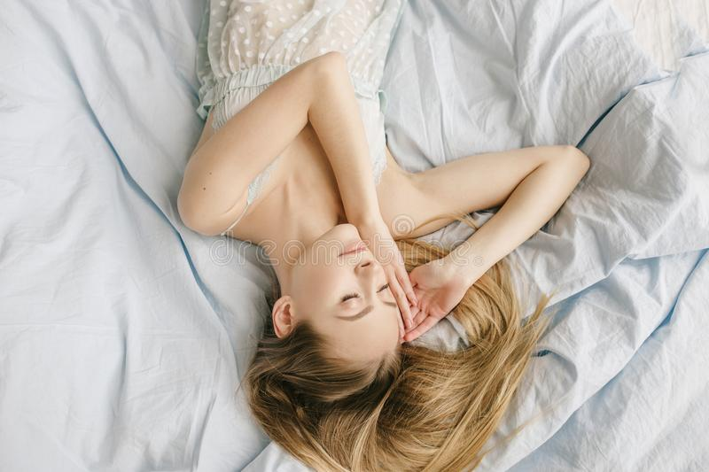 Beautiful young girl wearing light top and sleeping in the bedroom. Portrait of a young woman naps daytime sleep on the royalty free stock images