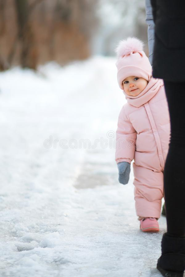 Beautiful young girl wearing a pink jumpsuit, peeking out from behind people in a snowy winter park royalty free stock images