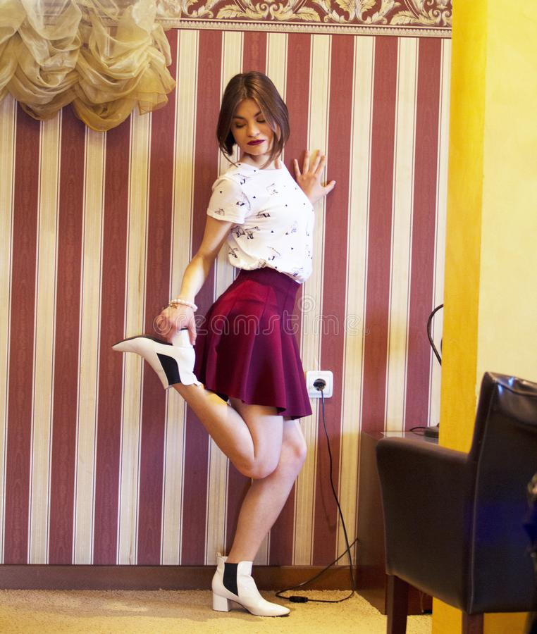 Beautiful young girl wearing a white t-shirt and red skirt, white shoes. stock images