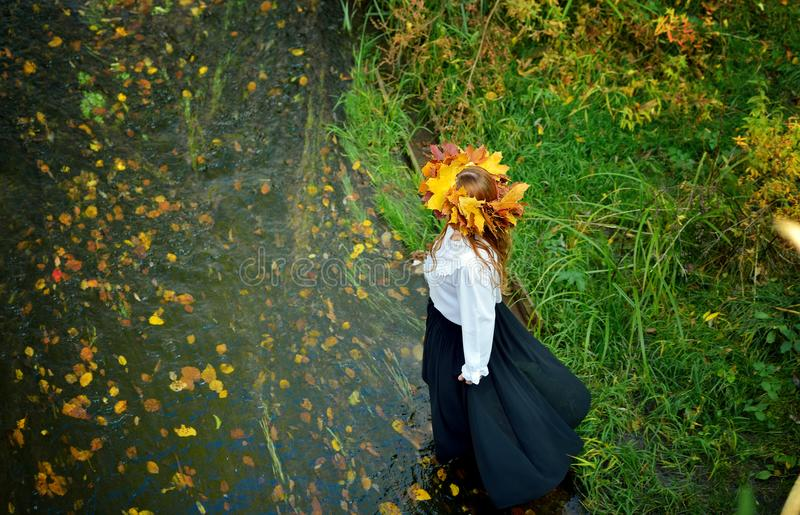 Beautiful young girl wearing a wreath of autumn leaves in a white shirt and black skirt enters the river. stock images
