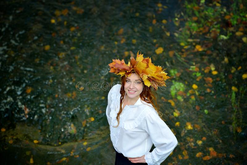 Beautiful young girl wearing a wreath of autumn leaves in a white shirt standing in the river royalty free stock photos