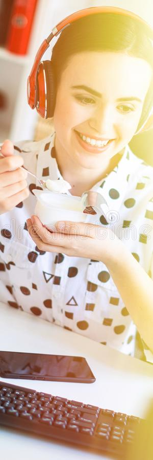 Beautiful young girl sitting in headphones at desk in office, eating yogurt and looking at monitor. royalty free stock photo