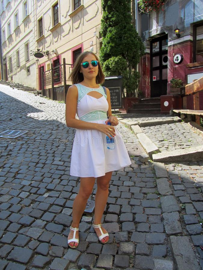 A beautiful young girl in a white dress and sunglasses, with a bottle of water walks along the cobblestone bridge. Of a European city stock image