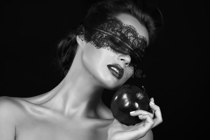 Beautiful young girl witch sorceress with a bandage black lace holding ripe apple magic witchcraft tempted to bite tale Sleeping royalty free stock image