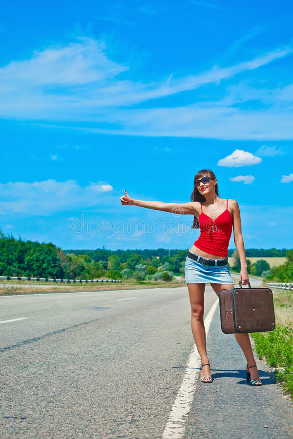 Beautiful young girl or woman in mini with suitcase hitchhiking along a road. Sunny day stock images