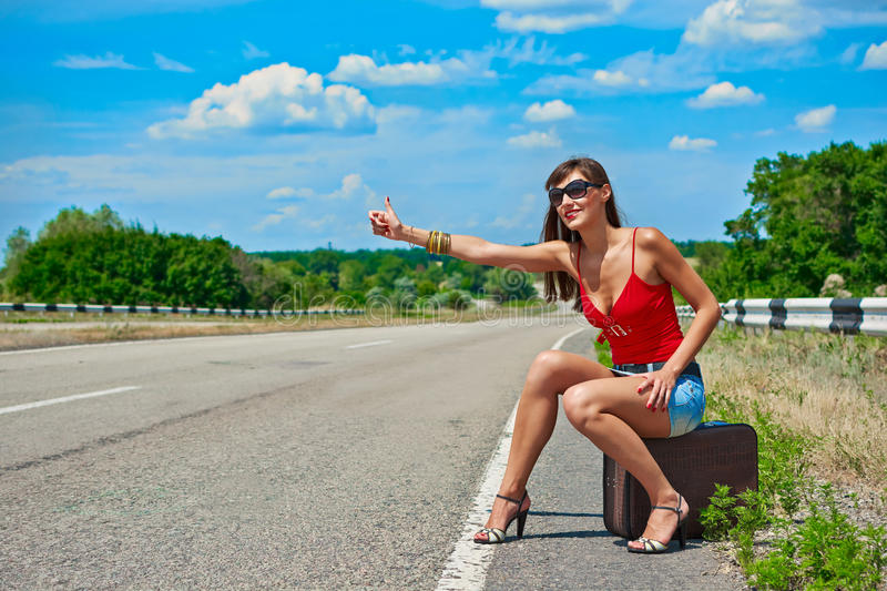 Beautiful young girl or woman in mini with suitcase hitchhiking along a road. Sunny day royalty free stock photography