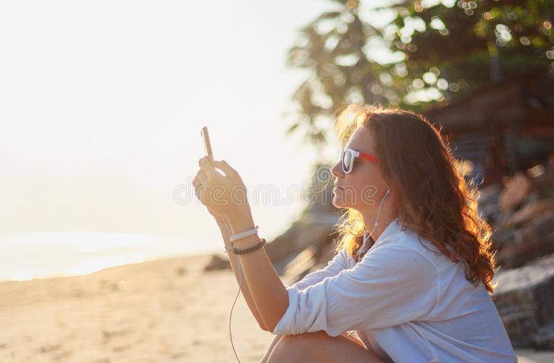 Beautiful young girl woman sitting on the beach at sunset in headphones and listening to music, rest and holidays. Beautiful young girl woman sitting on the royalty free stock photo