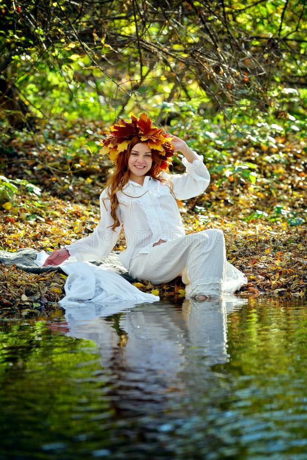 Beautiful young girl in a wreath from yellow leaves, in a white dress sitting by the water on a Sunny autumn day royalty free stock photography