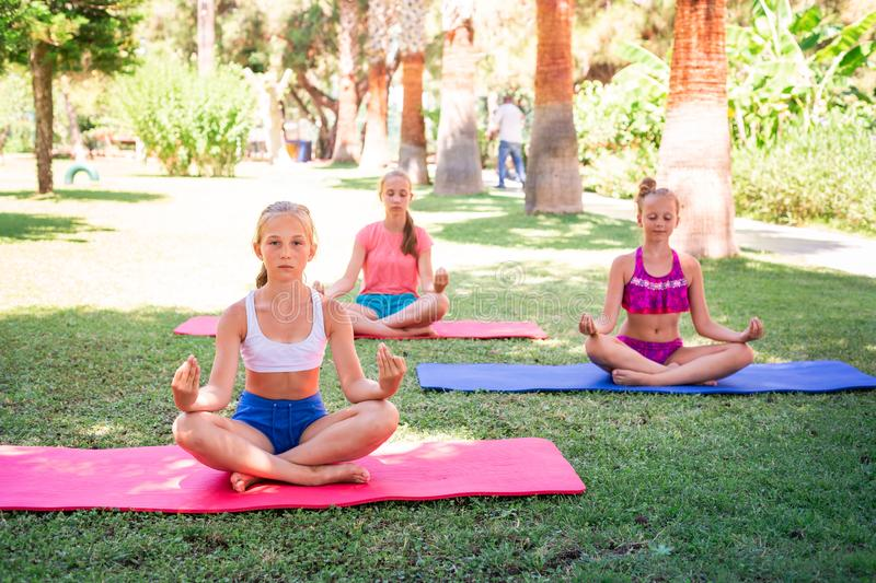 Beautiful young girls working out, exercising outdoor. Beautiful young girls working out, exercising, practicing yoga outdoor at the resort. Healthy lifestyle stock images